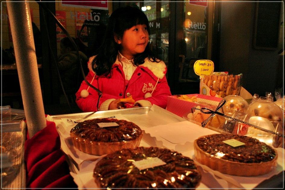 파이등을 파는 먹거리 가게 앞에 아이의 모습